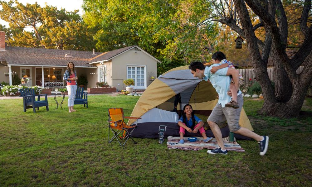 Dad and kids playing in a backyard with a tent in the background