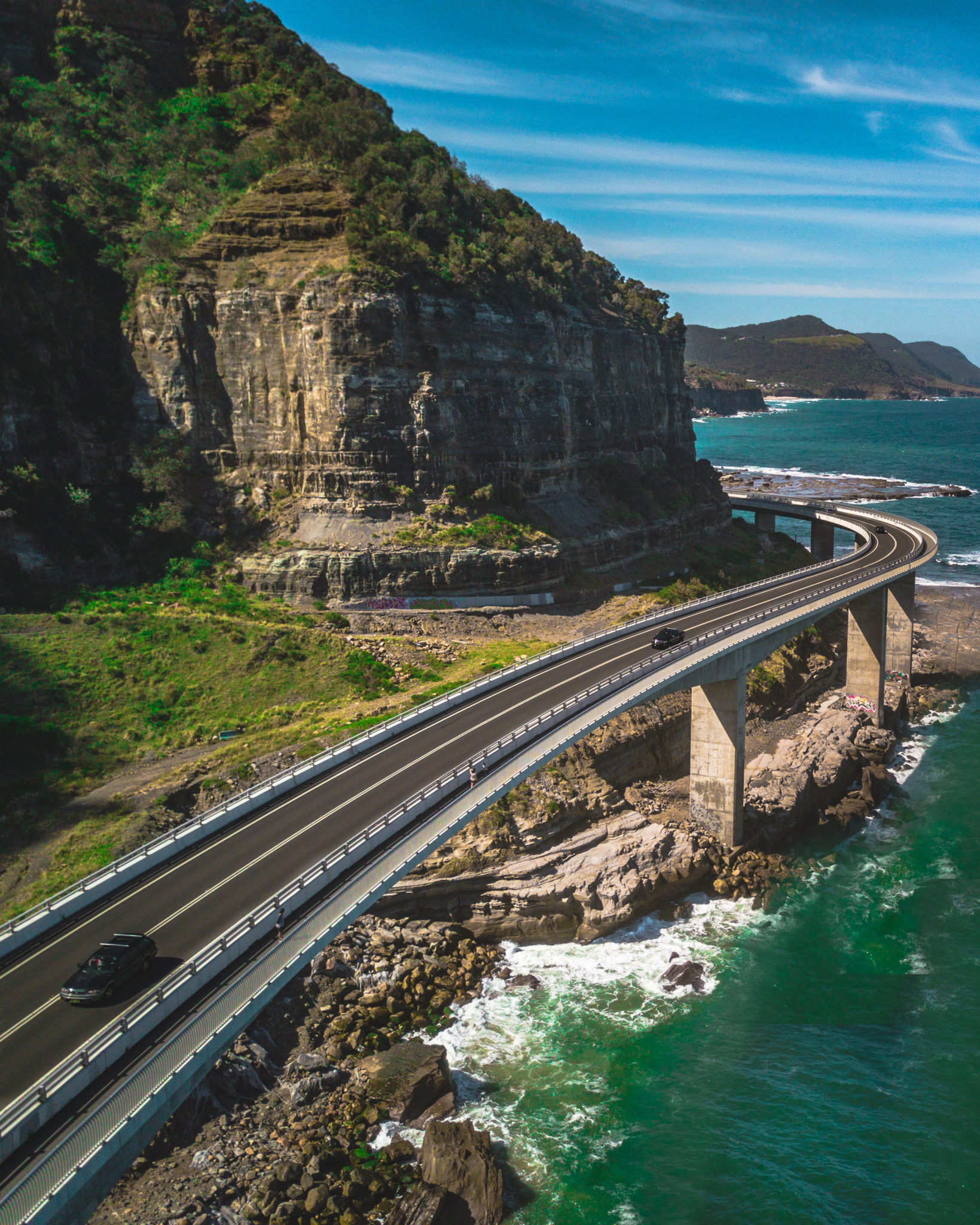 Road on the edge of the ocean rounding tall cliffs. Picture is for the Pacific Coast Highway Road Trip